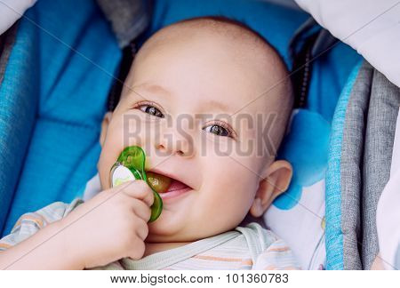 Happy Baby With Pacifier In A Stroller