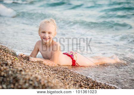 Happy Little Girl Lying On The Beach