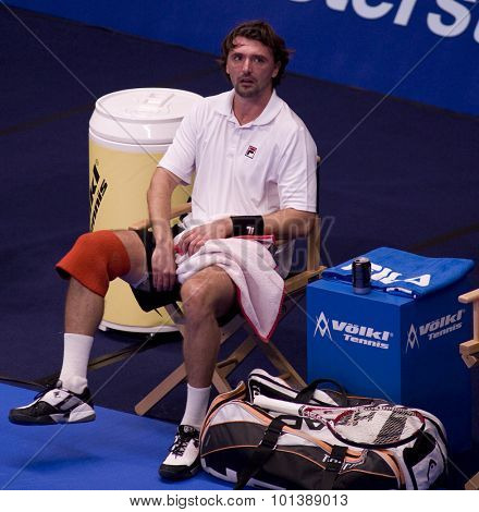 LONDON, ENGLAND. 05 DECEMBER 2009 -   Goran Ivanisevic (CRO) stretches his leg after pulling up while competing in the season finale to the ATP Champions Tour match between Rafter and Ivanisevic
