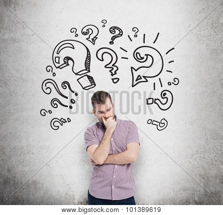 Young Man In Casual Shirt Holds His Chin And Thinks About Unsolved Problems. Question Marks Are Draw