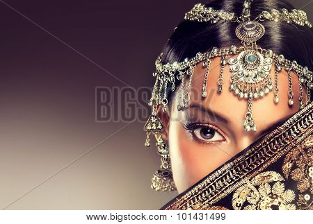 Mysterious Indian girl in traditional jewelry and black saree