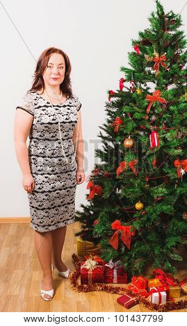 Middleage woman standing nearby Christmas tree