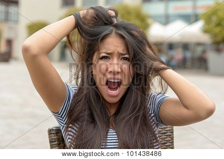 Upset Frantic Young Woman Tearing At Her Hair