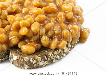 Beans on toast. Selective focus on beans placed on grain toast with a white background leaving room for copy space and text poster