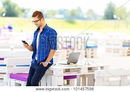 Pleasant guy holding mobile phone
