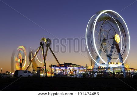 Colorful Carnival Ferris Wheel And Gondola Spinning In Motion Blurred At Twilight