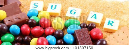 Heap of sweet candies and cookies with brown cane sugar and word sugar unhealthy food reduction of eating sweets poster