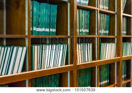 Green books on the bookshelf in university library, full of education knowledge