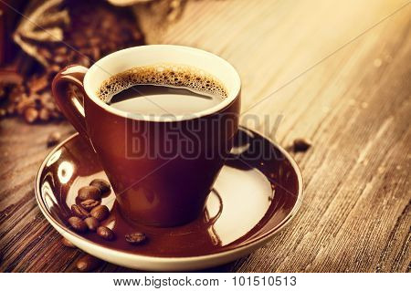Cup of aromatic coffee over wooden table close up. Cup of coffee with burlap sack full of roasted coffee beans over wood background. Vintage style. Traditional coffee