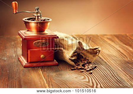 Coffee mill with burlap sack full of roasted coffee beans over wooden vintage table.  Coffee grinder with roasted coffee beans on wooden background. Coffee collection. Aroma