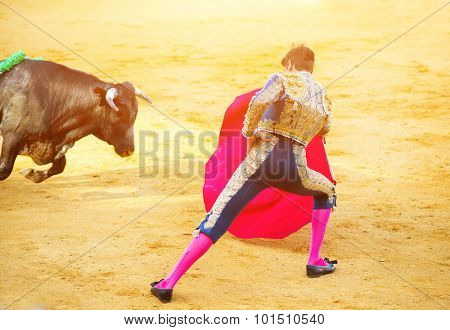 Traditional corrida - bullfighting in Spain. Matador in Ring with Bull. Spanish torero fighting on a bullring. Spanish national amusement