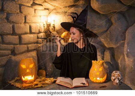 Beautiful young female wizard is practicing witchcraft