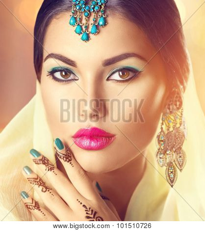 Beauty brunette Indian woman portrait. Hindu model girl with brown eyes, mehndi tattoo on hand and national Indian jewels looking in camera. Indian girl in sari. Marriage Traditions. Indian culture
