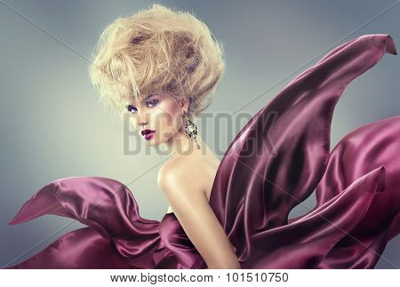 High fashion model girl portrait. Glamorous beauty woman with Updo hairstyle and bright makeup dressed in violet silk flying dress. Glamour Lady posing in studio