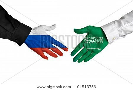 Russia and Saudi Arabia leaders shaking hands on a deal agreement