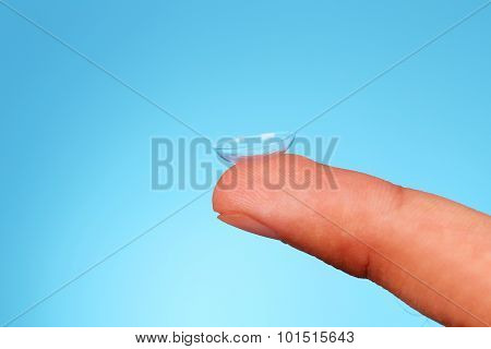 Contact Lens On Finger On Blue Background