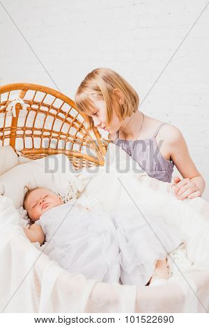 Beautiful girl sits nearby cradle with sleeping baby