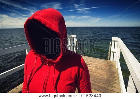 Faceless Hooded Unrecognizable Woman At Ocean Pier, Abduction Concept