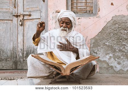 Old indian sadhu reading scriptures.
