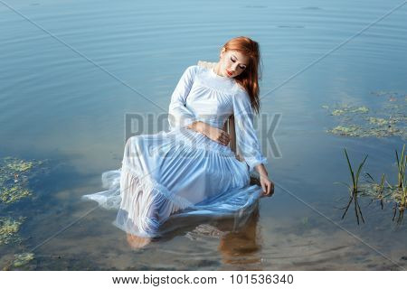Girl White Dress Sitting On Chair In A Lake.