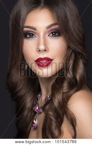 Beautiful woman with arabic make-up, red lips and curls. Beauty face. Picture taken in the studio on a gray background. poster