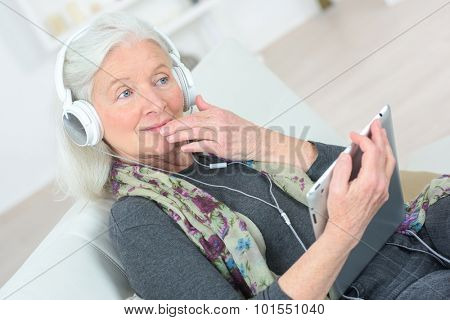 Senior lady listening to music through headphones