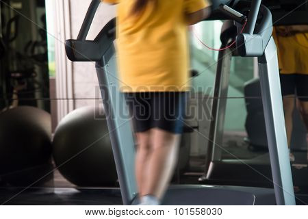 Motion Blur Of Woman In Yellow Shirts And Black Sport Shorts Run In Finess Using Tread Mill