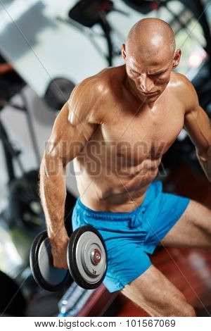 Young man doing a triceps workout with dumbbells in gym poster