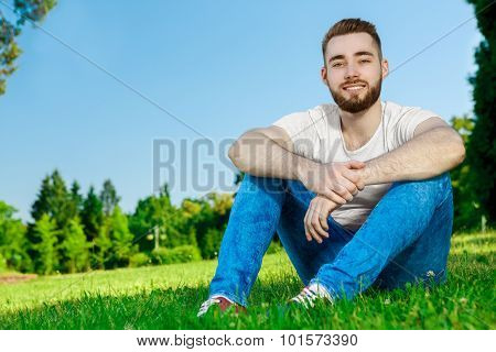 Young man sitting on the grass in park