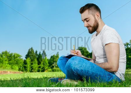Young man sitting on the grass in park with diary