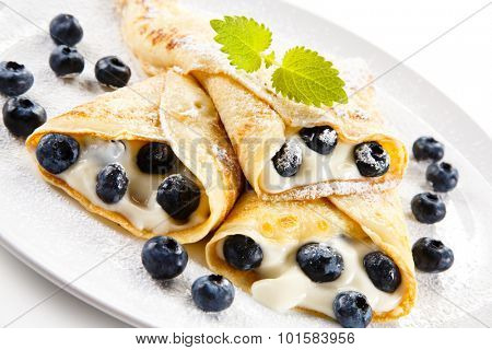 Crepes with blueberries and cream on white background