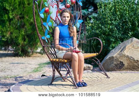 The Girl Sits On A Shod Park Bench.