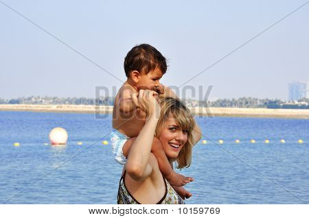 Happy Mother And Son Playing On The Beach