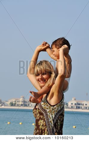 Happy Mother And Son Playing On The Beach At Sunset