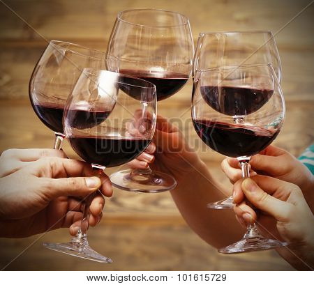 Clinking glasses of red wine in hands on rustic wooden planks background