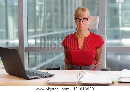 caucasian business woman in eyeglasses relaxing, stretching back - short break for exercise on chair  in office poster