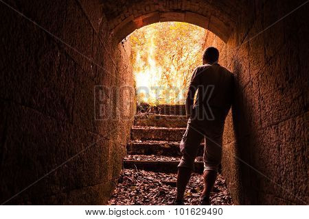 Young Man Stands In Dark Stone Tunnel With Big Fire
