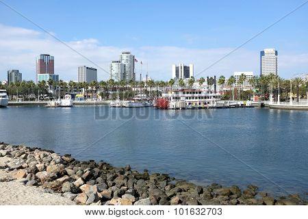 LONG BEACH, CA - FEBRUARY 21, 2015: Rainbow Harbor and city skyline. The harbor cruise boat Grand Romance  river boat at dock in Rainbow Harbor with city skyline in background.