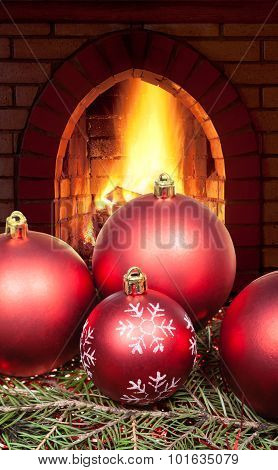 Red Christmas Balls On Spruce Tree And Fireplace