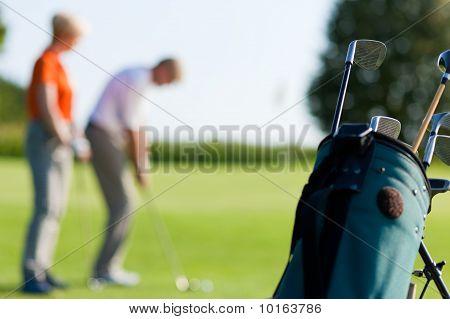 Mature couple playing Golf (focus on bag)