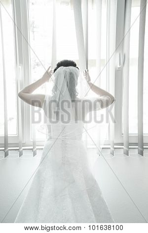 Bride on a window looking for a groom. Wedding concept