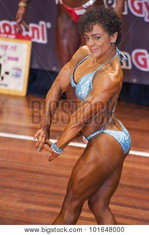 Female Bodybuilder In Chest Pose With Blue Bikini