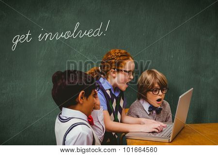 The word get involved! and pupils using laptop against green chalkboard