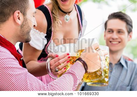 Three friends in Munich Beer garden clinking glasses wearing traditional Tracht