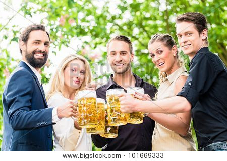 Friends or colleagues on beer garden after work toasting with drinks poster