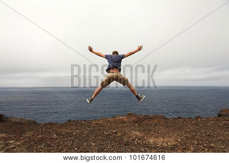 Freedom or adventure concept - jump of young man from a seaside cliff