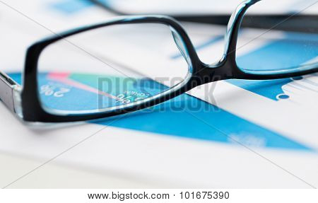 business, objects and statistics concept - close up of eyeglasses and files on office table