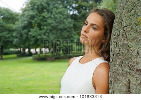 sad young woman leaning against tree