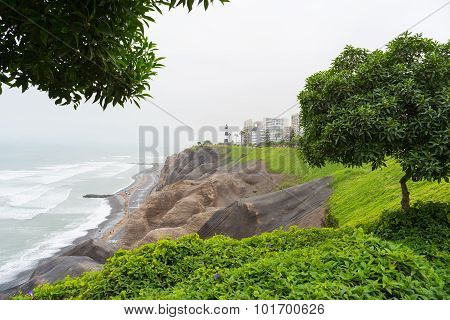 Dramatic coastline in Lima Miraflores viewed from above. Winter season cloudy and foggy sky waving ocean. Skyline in the background. poster