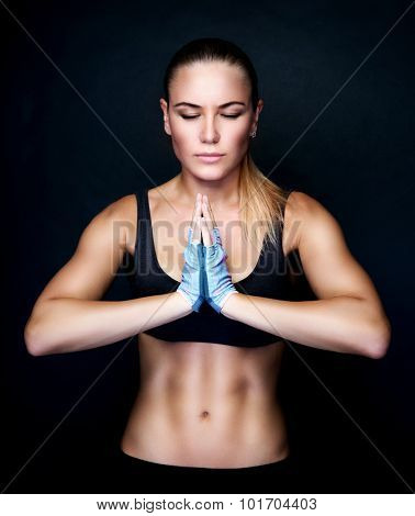 Beautiful woman meditating in the studio, doing yoga exercises over black background, sportive lifestyle, healthy active life
